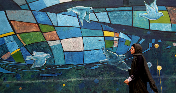 An Iranian woman walks past colourful walls in the capital Tehran on November 5, 2018