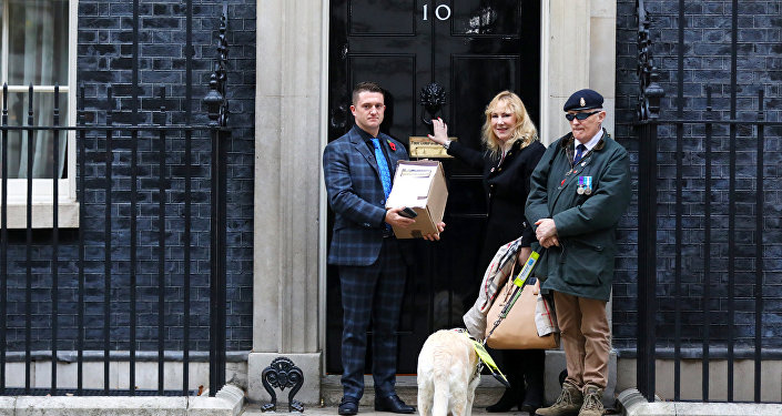 Stephen Yaxley-Lennon, who goes by the name Tommy Robinson, poses outside 10 Downing Street with MEP Janice Atkinson as he hands in a petition on behalf of a serving soldier who was disciplined for posing for a selfie with him, in London, Britain, November 6, 2018.