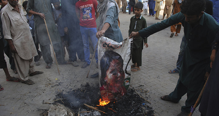 Pakistani protesters burn a poster image of Christian woman Asia Bibi, who has spent eight-years on death row accused of blasphemy and acquitted by a Supreme Court, in Hyderabad, Pakistan, Thursday, Nov. 1, 2018