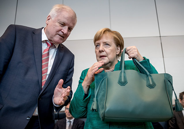 German Chancellor and leader of the Christian Democratic Union (CDU) Angela Merkel holds her hand bag as she confers with German Interior Minister Horst Seehofer at the beginning of a session on September 25, 2018 in the parliamentary compound of the Bundestag, where the parliamentary group is to elect their president