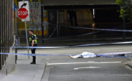 A policeman stands near a body covered with a sheet near the Bourke Street mall in central Melbourne, Australia, November 9, 2018