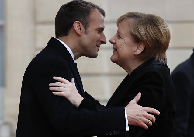French President Emmanuel Macron hugs German Chancellor Angela Merkel in the courtyard of the Elysee Palace. File photo