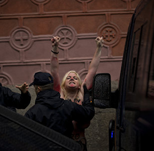 An activist from the women's movement Femen is dragged away by a police officer while they protest near a demonstration against the abortion in Madrid, Spain, Sunday, Oct. 17, 2013