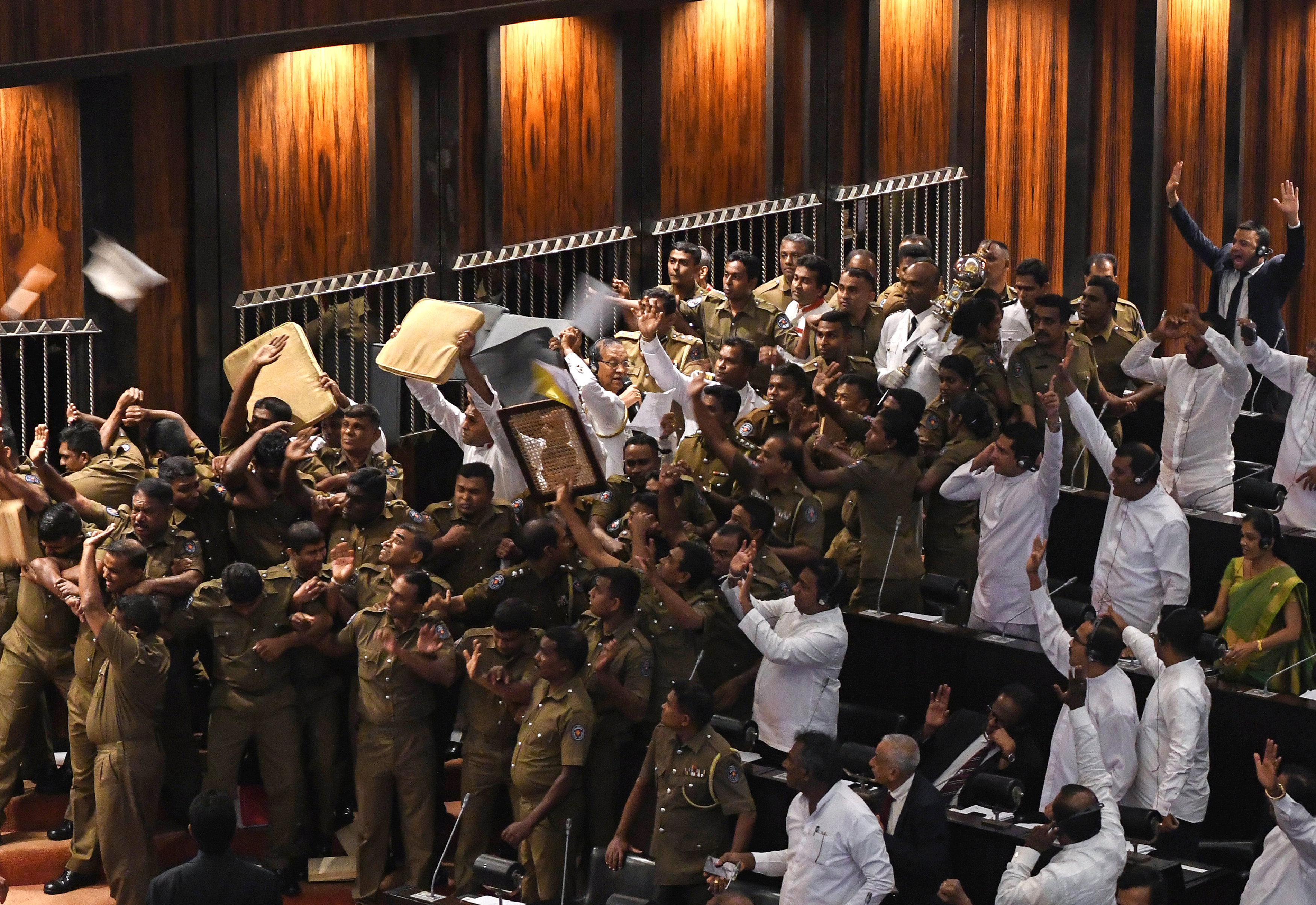 Sri Lankan police escort parliament speaker Karu Jayasuriya (C holding microphone) as aides hold up cushions to protect him and themselves from projectiles thrown by rival legislators in the assembly hall in Colombo on November 16, 2018