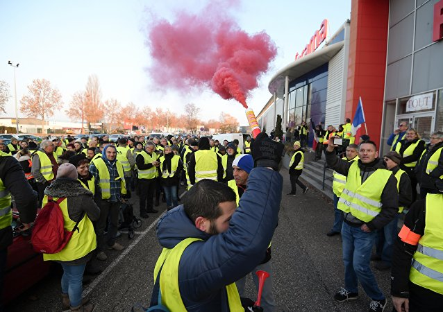 A demonstrator holds a flare during a demonstration of Yellow Vests (Gilets jaunes) against the rising of the fuel and oil prices on November 17, 2018 in Vendenheim, eastern France.