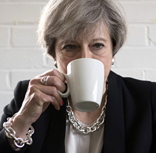 Britain's Prime Minister Theresa May drinks from a mug as she meets youth activists during a visit to the Young Minds mental health charity while on the election campaign trail, in London, Thursday May 11, 2017. Britain will hold a general election on June 8.