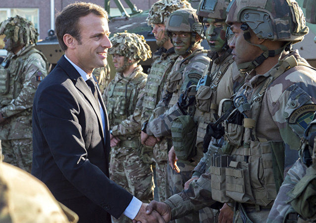 FILE - In this Friday, Sept. 29, 2017 file photo, France's President Emmanuel Macron, left, shakes hands with French soldiers of the NATO Battle Group at the Tapa military base, about 90 kilometers (56 miles) west of Tallinn, Estonia