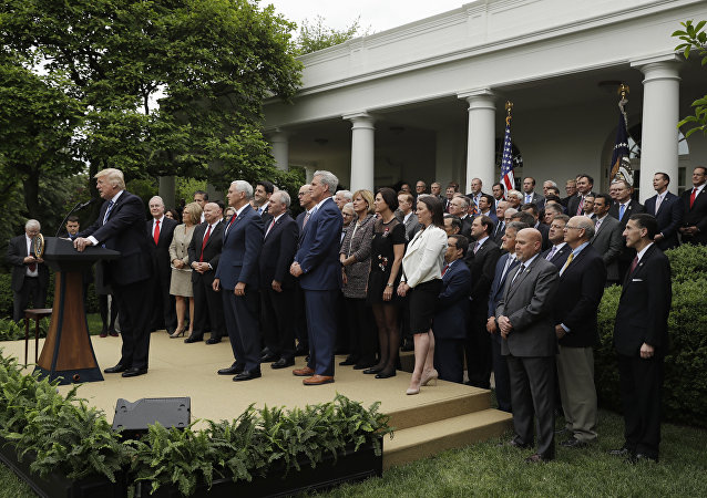 President Donald Trump, accompanied by House GOP members, speaks in the Rose Garden of the White House in Washington, Thursday, May 4, 2017, after the House pushed through a health care bill