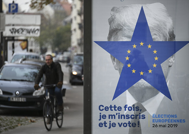 A cyclist rides near a street poster depicting the twelve-star circle from the European Union flag within a blue five-pointed star covering the face of what is deemed to be a portrait of US President Donald Trump, and a text reading in This time, I register and I vote, on November 21, 2018, in Strasbourg, eastern France, ahead of European Elections in May 2019.