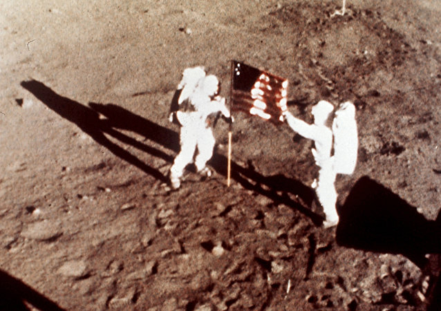 Apollo 11 astronauts Neil Armstrong and Edwin E. Buzz Aldrin, the first men to land on the moon, plant the U.S. flag on the lunar surface, July 20, 1969. Photo was made by a 16mm movie camera inside the lunar module, shooting at one frame per second
