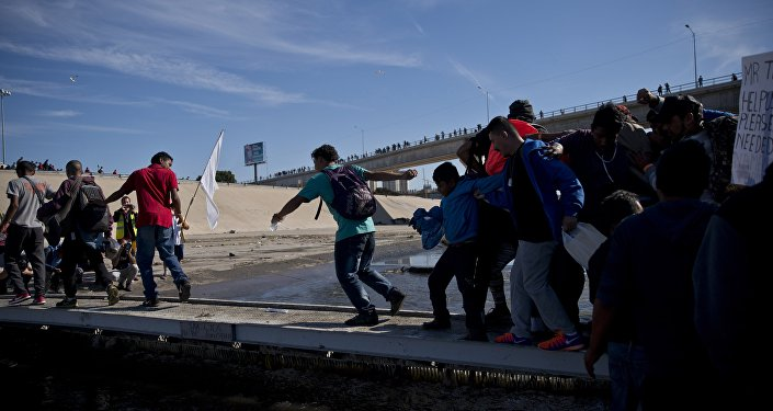 Migrants cross the river at the Mexico-U.S. border after getting past a line of Mexican police at the Chaparral crossing in Tijuana, Mexico, Sunday, Nov. 25, 2018
