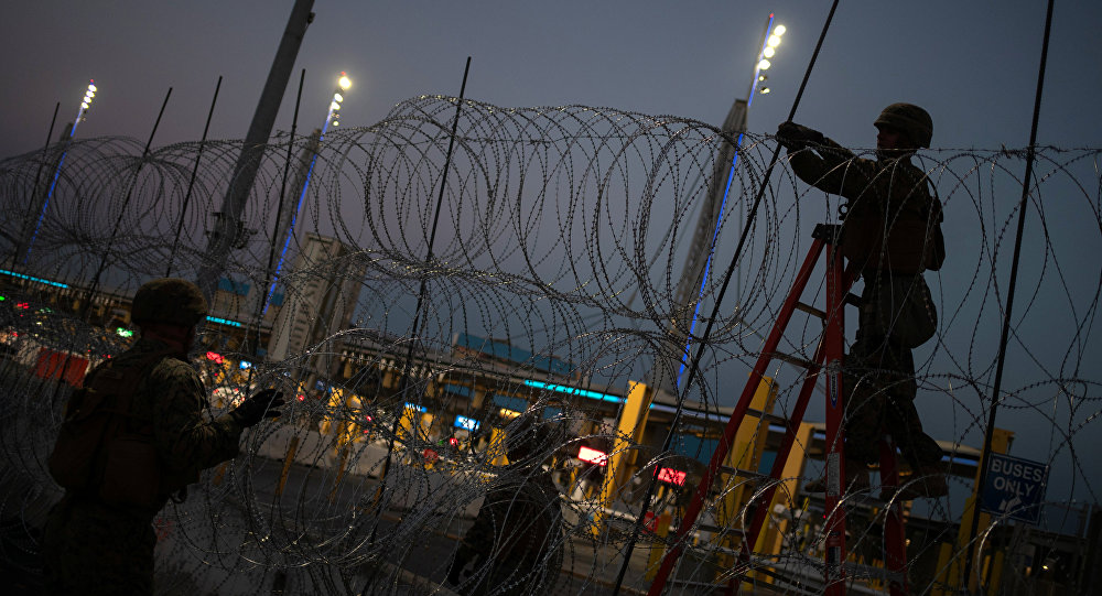 United States Marines fortify concertina wire along the San Ysidro Port of Entry border crossing as seen from Tijuana