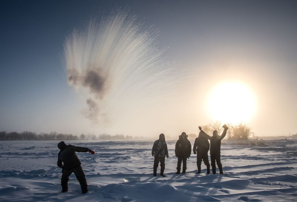 A villager throws hot water into the air while harvesting ice in Siberia