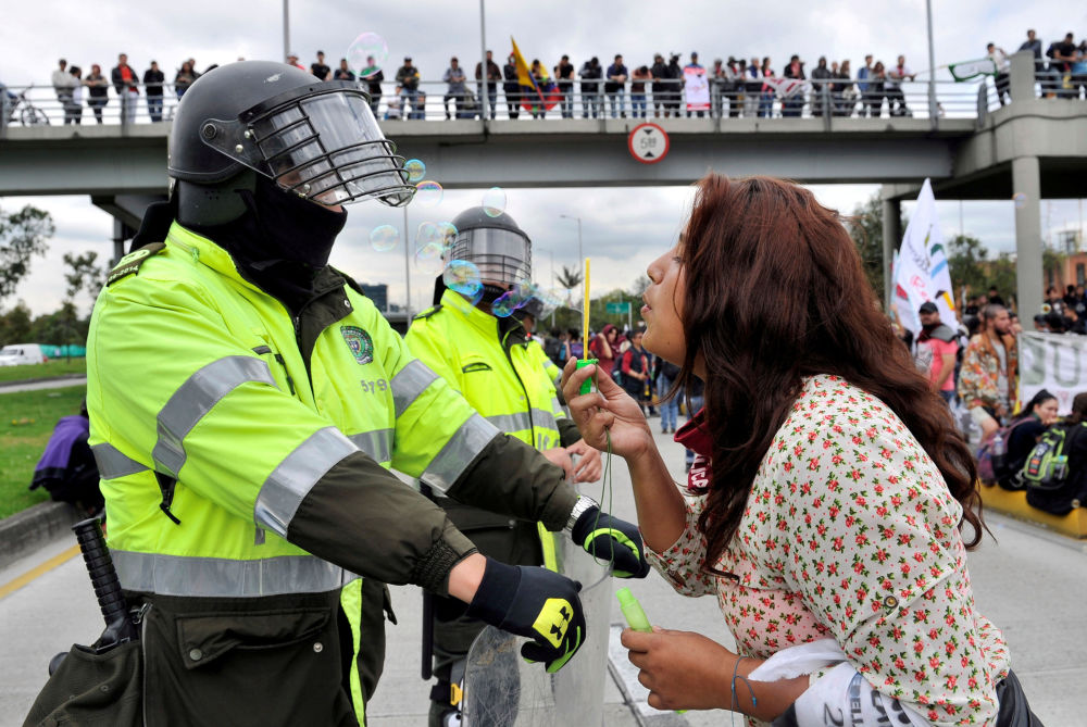 A student blows soap bubbles at a policeman during a school funding march in Colombia