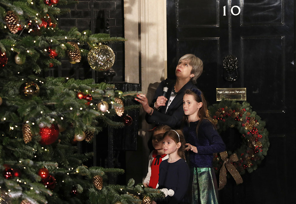Britain's Prime Minister Theresa May stands with children as she switches on the Christmas tree lights at 10 Downing Street in London, Wednesday, Dec. 6, 2017.