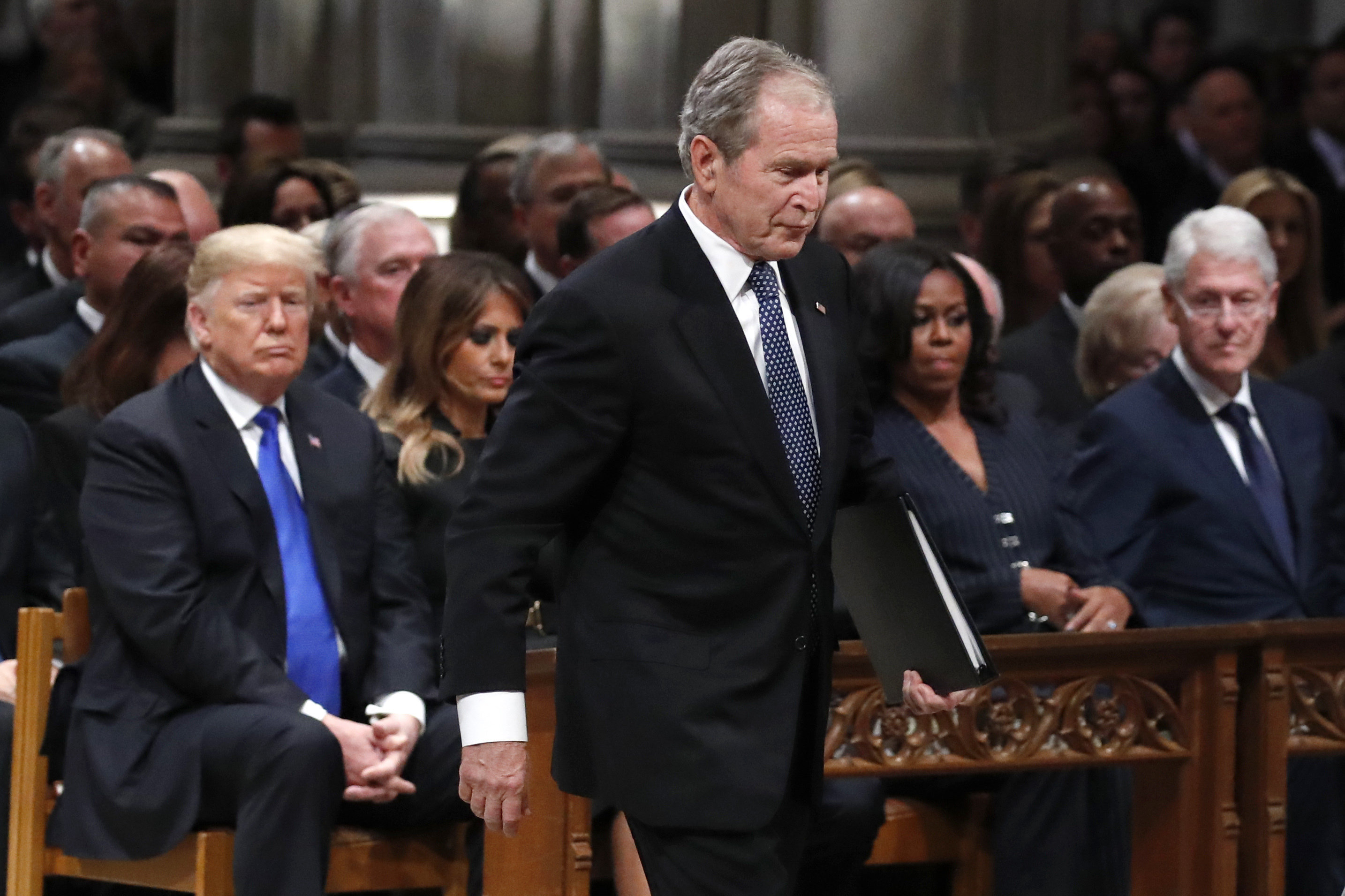 Former President George W. Bush walks past President Donald Trump, first lady Melania Trump, Michelle Obama and former President Bill Clinton to give a eulogy for his father