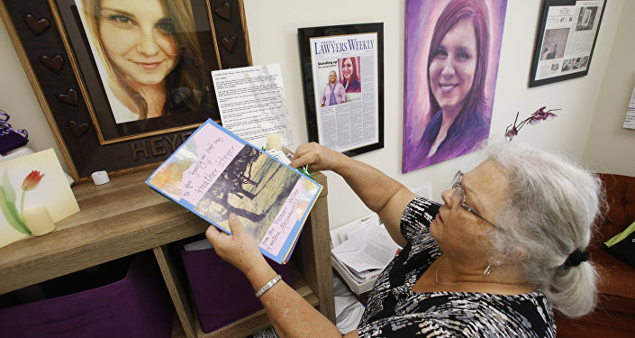 In this Monday, Aug. 6, 2018 photo, Susan Bro, mother of Heather Heyer, who was killed during the Unite the Right rally last year, looks over memorabilia in her office in Charlottesville, Va