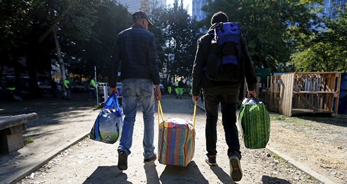 Migrants carry their belongings as they leave a makeshift camp for refugees outside the foreign office in Brussels, Belgium October 2, 2015