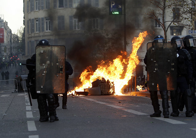 Riot police officer stand in front a burning trash bin during clashes, Saturday, Dec. 8, 2018 in Marseille, southern France