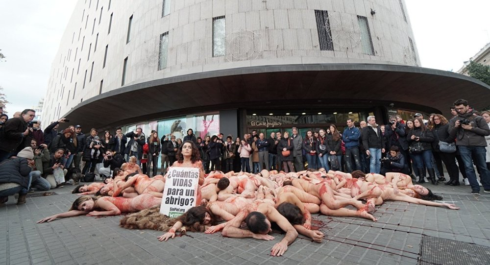 Animal rights activists can be seen staging a protest against the fur industry in Barcelona on 16 December 2018