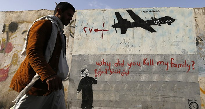 A man walks past a graffiti, denouncing strikes by U.S. drones in Yemen, painted on a wall in Sanaa, Yemen