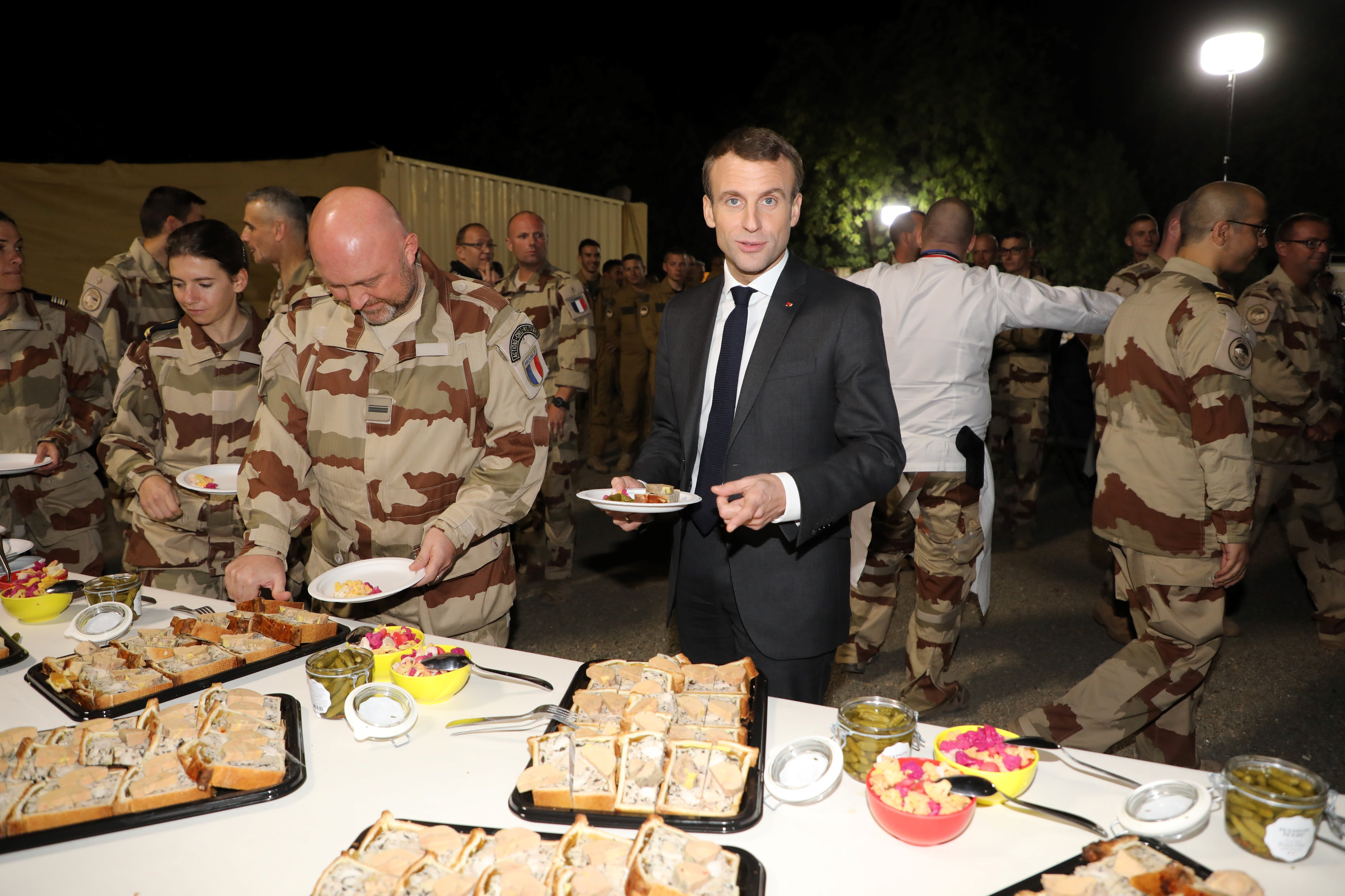 French president Emmanuel Macron eats dinner with soldiers the Barkhane force at the Barkhane tactical command centre in N'Djamena on December 22, 2018.
