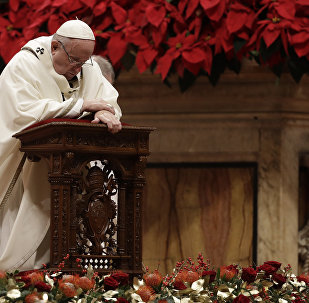 Pope Francis kneels on the altar as he celebrates the Christmas Eve Mass in St. Peter's Basilica at the Vatican, Monday, Dec. 24, 2018