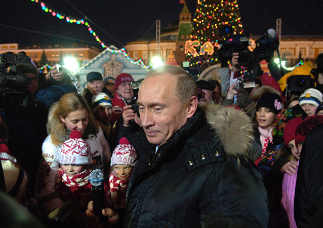 Russian President Vladimir Putin talks to children while visiting the Red Square skating rink next to the Kremlin (File)