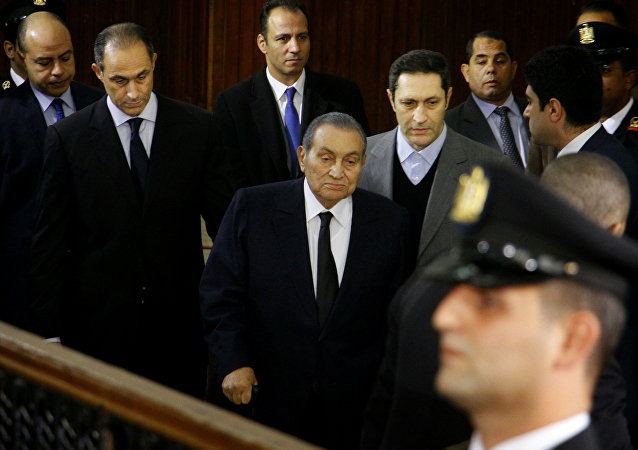 Former Egyptian President Hosni Mubarak, center, arrives with his sons Alaa, left, and Gamal, right, to testify, in a courtroom at the National Police Academy in Cairo, Egypt, Wednesday, Dec. 26, 2018.