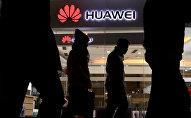 Pedestrians walk past a Huawei retail shop in Beijing Thursday, Dec. 6, 2018