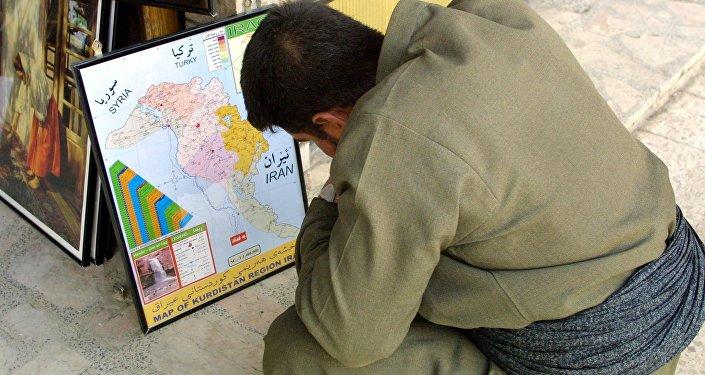 An Iraqi Kurd observes the kurdish enclave on an Iraqi map (File)