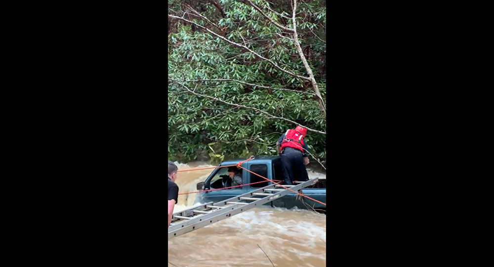 First responders in Tennessee work to rescue woman and child from a swollen creek.