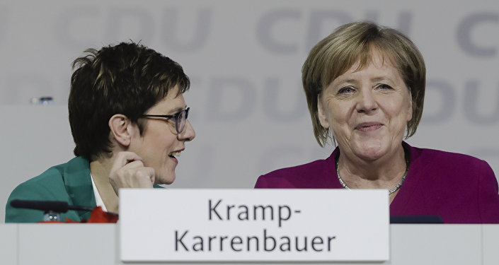 German Chancellor Angela Merkel, right, talks with CDU party chairwoman Annegret Kramp-Karrenbauer, left, during a party convention of the Christian Democratic Party CDU in Hamburg, Germany, Saturday, Dec. 8, 2018