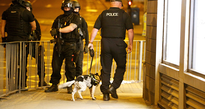 Armed police officers stand near the Manchester Arena