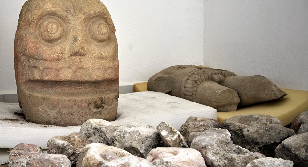 In this 2018 photo provided by Mexico's National Institute of Anthropology and History, INAH, a skull-like stone carving and a stone trunk depicting the Flayed Lord, a pre-Hispanic fertility god depicted as a skinned human corpse, are stored after being excavated from the Ndachjian–Tehuacan archaeological site in Tehuacan, Puebla state, where archaeologists have discovered the first temple dedicated to the deity.