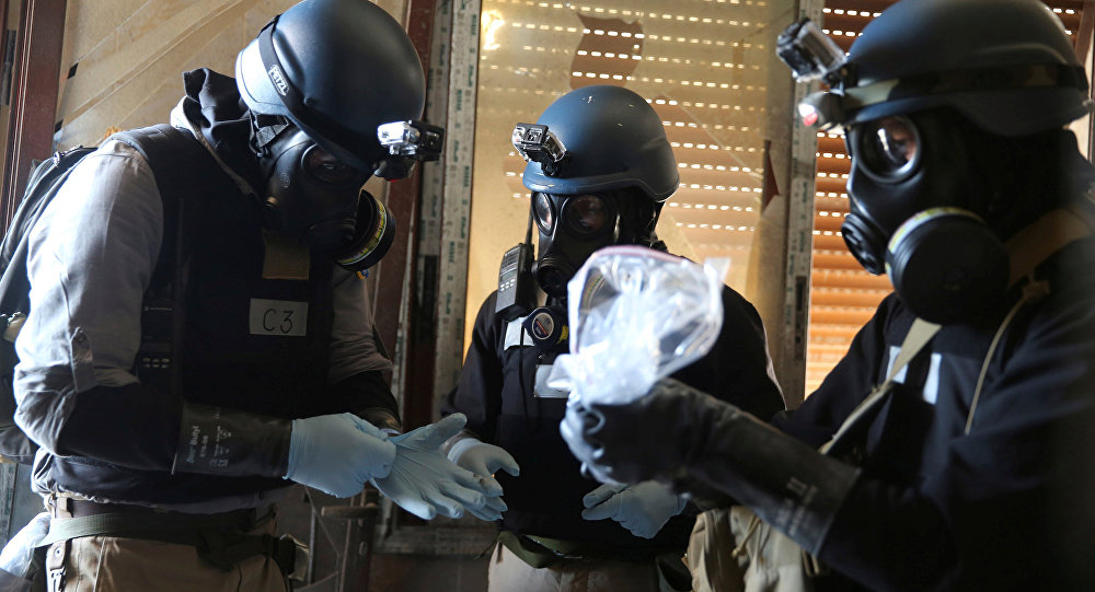 A U.N. chemical weapons expert, wearing a gas mask, holds a plastic bag containing samples from one of the sites of an alleged chemical weapons attack in the Ain Tarma neighbourhood of Damascus, Syria. (File)