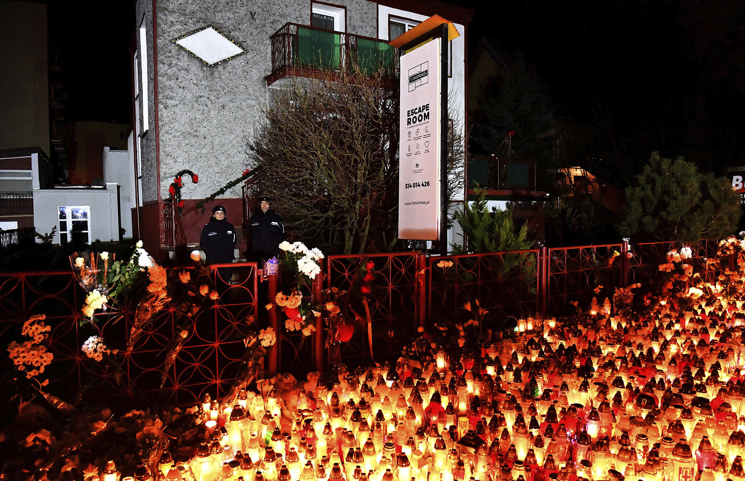 Lights, flowers and toys are left outside the escape room entertainment site where five teenage girls died in a fire last week, in Koszalin, northern Poland, on Sunday, Jan. 6, 2019. Sunday was designated a day of mourning and prayers in Koszalin for the girls and their families.