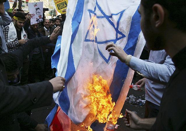 Demonstrators burn representations of Israeli and the U.S. flags during a rally in front of the former U.S. Embassy in Tehran, Iran, on Sunday, Nov. 4, 2018