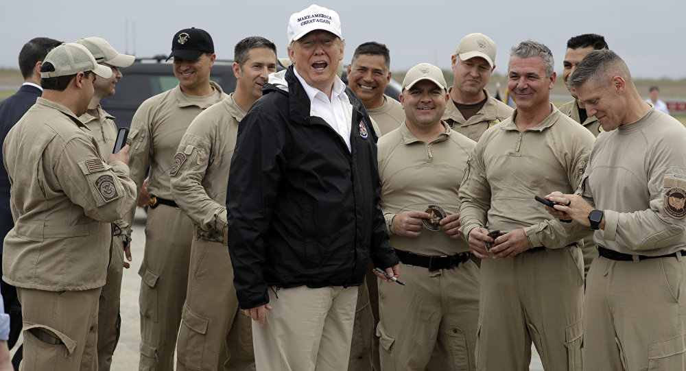 President Donald Trump turns as he talks to U.S. Customs and Border Protection officers at McAllen International Airport as he prepares to leave after a visit to the southern border, Thursday, Jan. 10, 2019, in McAllen, Texas
