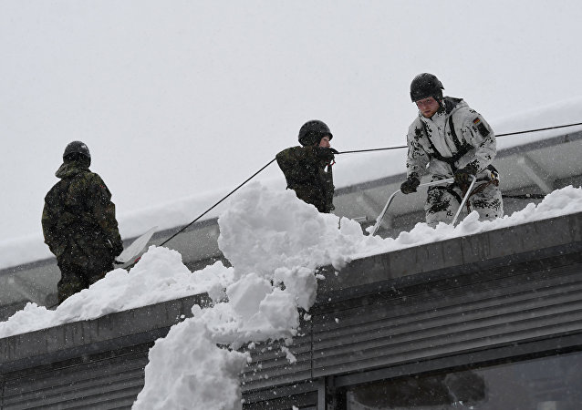 Soldiers of the German armed forces Bundeswehr remove snow from the roof of a high school building in Berchtesgaden, Germany, January 10, 2019