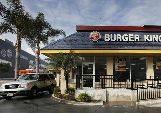 FILE - In this Thursday, April 25, 2013, file photo, a car stops at the drive-thru at a Burger King restaurant near downtown Los Angeles. Restaurant Brands International, the parent company of Burger King and Tim Hortons, reports financial results Monday, Oct. 24, 2016.