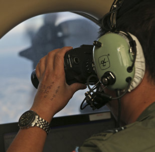 In this March 22, 2014, file photo, Flight Officer Jack Chen uses binoculars at an observers window on a Royal Australian Air Force P-3 Orion during the search for missing Malaysia Airlines Flight MH370 in Southern Indian Ocean, Australia