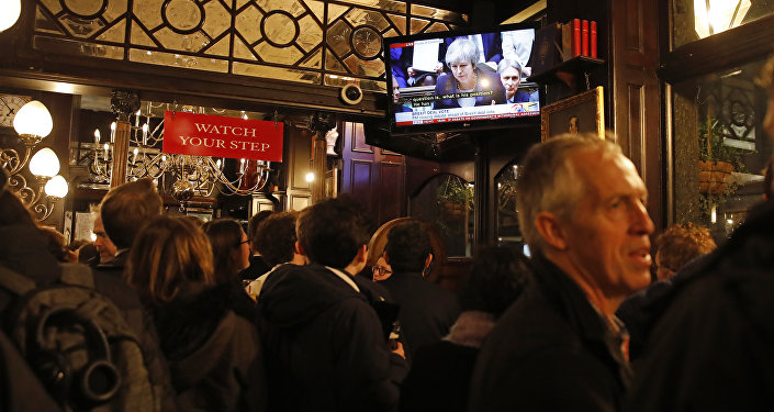 Drinkers watch a television screen in the Red Lion public house on Whitehall, as it shows Britain's Prime Minister Theresa May speaking in the House of Commons in London on January 15, 2019, before MPs vote on the government's Brexit deal