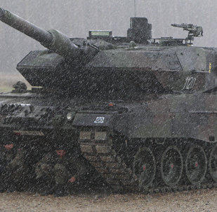 Polish troops take shelter from pouring rain under the belly of a tank during a ceremony welcoming a deployment of new NATO troops in Orzysz, northeast Poland