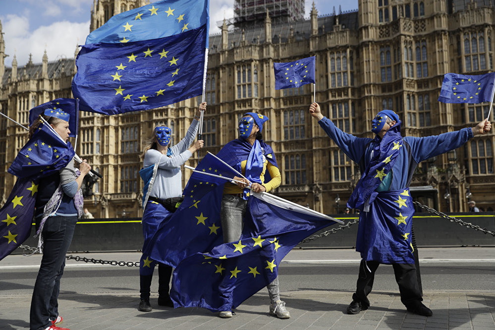 Pro-remain supporters of Britain staying in the EU, wear EU flag masks as they take part in an anti-Brexit protest outside the Houses of Parliament in London, Monday, Sept. 11, 2017. Lawmakers are due to vote late Monday or early Tuesday on the European Union (Withdrawal) Bill, which aims to convert around 12,000 EU laws and regulations into domestic statute on the day the country leaves the bloc in March 2019