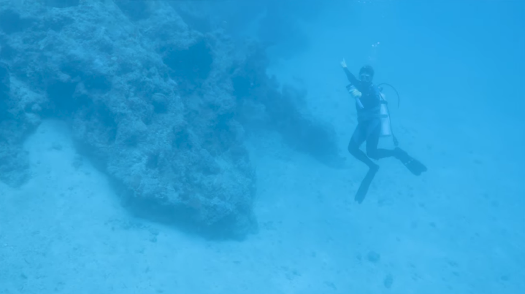 Local diver points toward aircraft suspected of being Amelia Earhart's Lockheed Electra 10E