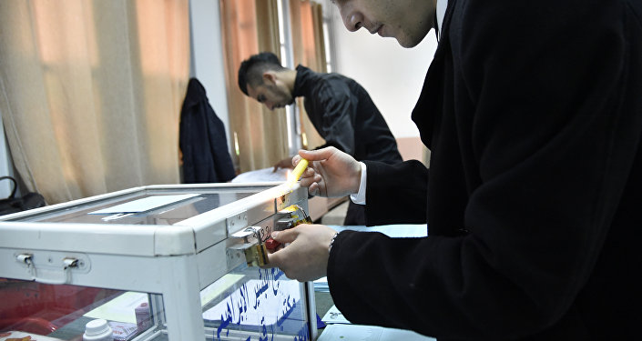 An electoral official works on a ballot box at a polling station in Algiers on November 23, 2017 as Algeria goes to the polls for local elections.