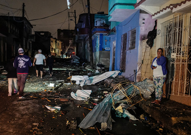 Cubans walk past debris in the tornado-hit Luyano neighbourhood in Havana early on January 28, 2019