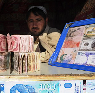 A Pakistani man holds banknotes as he waits for the customers at his currency exchange shop in Quetta on November 22, 2010