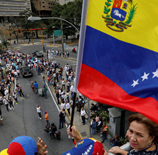 A supporter of Venezuelan opposition leader and self-proclaimed interim president Juan Guaido holds a flag while taking part in a protest against Venezuelan President Nicolas Maduro's government in Caracas, Venezuela January 30, 2019.